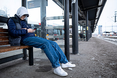 Teenage boy waiting at train station - p1687m2278458 by Katja Kircher