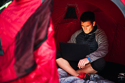 Man camping in Estonia, sitting in tent, using laptop - p300m2219354 by Kike Arnaiz