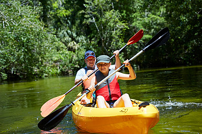 Smiling girl with father canoeing with oar in lake - p300m2273675 by Stefanie Aumiller