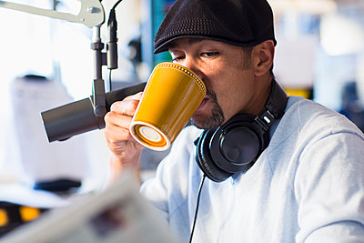Mixed race disc jockey drinking cup of coffee in studio - p555m1454019 by Marc Romanelli