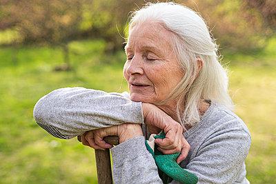 Senior woman relaxing in garden - p623m2164919 by Frederic Cirou