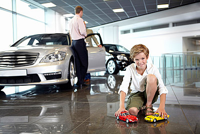 Boy playing with toy cars in automobile showroom - p64114764f by Adam Gault