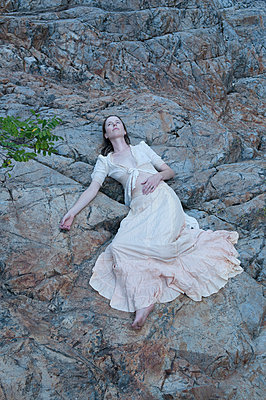 Woman lying on the rocks - p920m917761 by Jude Mooney