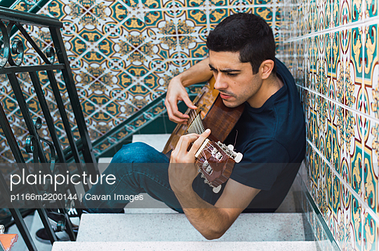 Focus man playing guitar sitting on a staircase with beautiful tiles. - p1166m2200144 by Cavan Images