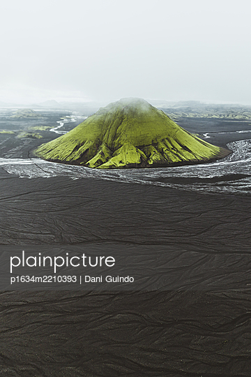 Green volcano surrounded by a vast black sand dessert - p1634m2210393 by Dani Guindo