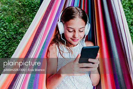 beautiful kid girl lying on hammock and using mobile phone, summertime, Madrid, Spain - p300m2287300 von Eva Blanco