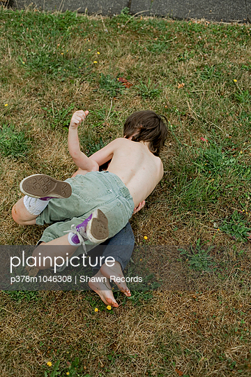 Two shirtless boys wrestling in the grass. Portland, Oregon, U.S.A