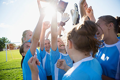 middle school girl soccer team celebrating and cheering with trophy - p1192m1173898 by Hero Images