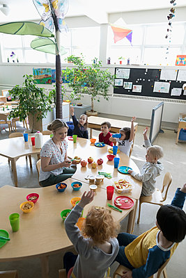 Preschool teacher and students eating during snack time in classroom - p1192m1560199 by Hero Images