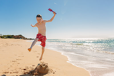 Boy playing and jumping on the beach - p300m1205385 by Nicole Matthews