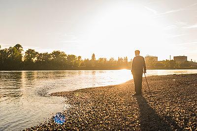 Back view of senior man standing at riverside watching sunset - p300m1460208 by Uwe Umstätter
