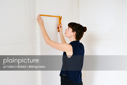 Junge Frau misst Wand mit Zollstock  - p1124m1160243 von Willing-Holtz