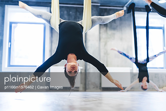 Women hanging from hammocks while practicing anti-gravity yoga in gym - p1166m1576462 by Cavan Images