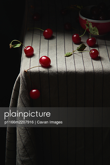 Ripe juicy red cherries are scattered on the table - p1166m2207916 by Cavan Images