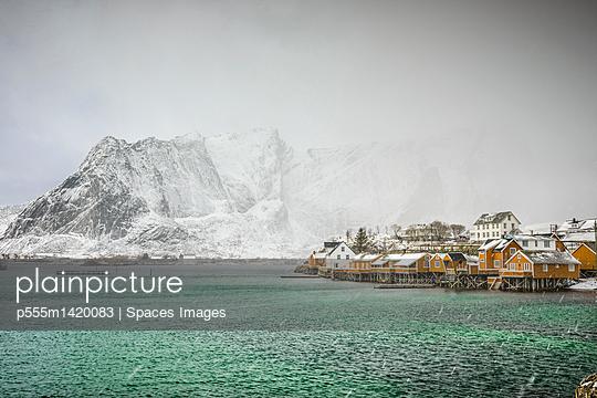 Snowy mountains overlooking rocky coastline, Reine, Lofoten Islands, Norway - p555m1420083 by Spaces Images
