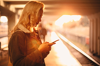 Young woman using smart phone waiting for train at subway station - p1166m2153524 by Cavan Images