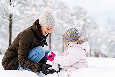 Happy mother playing with daughter in winter landscape - p300m2083152 by Daniel Ingold