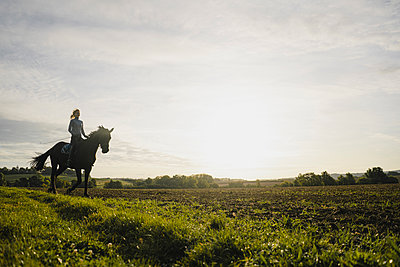 Woman riding horse on a field in the countryside at sunset - p300m2155373 by Joseffson