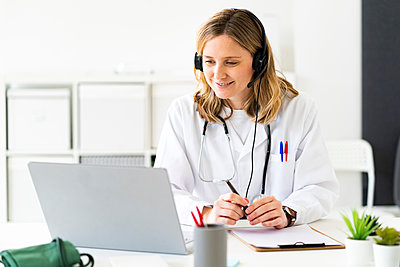 Blond female doctor giving online consultation on laptop in medical clinic - p300m2266173 by Giorgio Fochesato