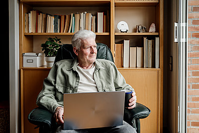 Senior man looking away while holding laptop at home - p300m2281363 by VITTA GALLERY