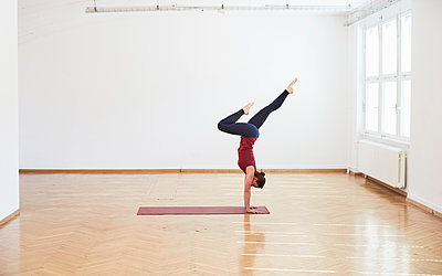 Side view of woman in exercise studio doing handstand - p429m1179697 by Stephen Lux