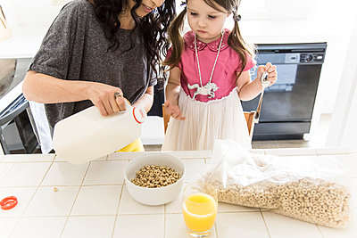 Caucasian mother and daughter eating cereal in kitchen - p555m1311492 by Andie Mills