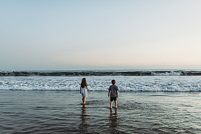 Siblings walking into the ocean staring at the horizon at sunset - p1166m2136537 by Cavan Images