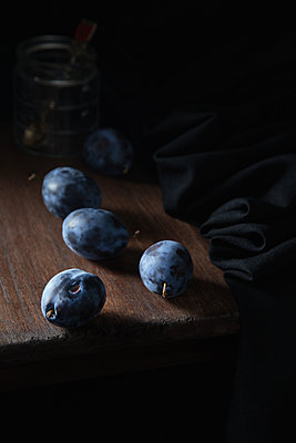 Blue plum on a wooden table against the background of a glass jar - p1166m2212258 by Cavan Images
