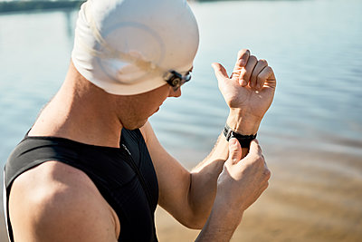 Young athlete swimmer in rubber cap puts on watch standing on river - p1630m2196901 by Sergey Mironov