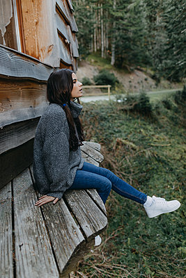 Young woman sitting at a wooden house in the nature - p300m1550136 by Oriol Castelló Arroyo