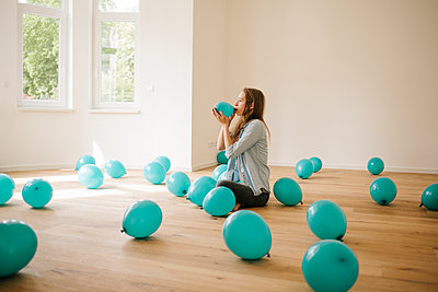 Young woman in new apartment playing with balloons - p586m1064881 by Kniel Synnatzschke