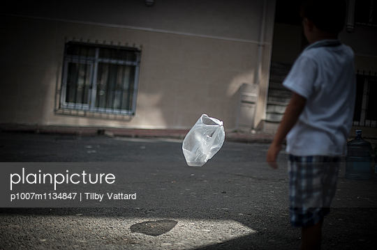 Boy playing with flying plastic bag in sun light - p1007m1134847 by Tilby Vattard
