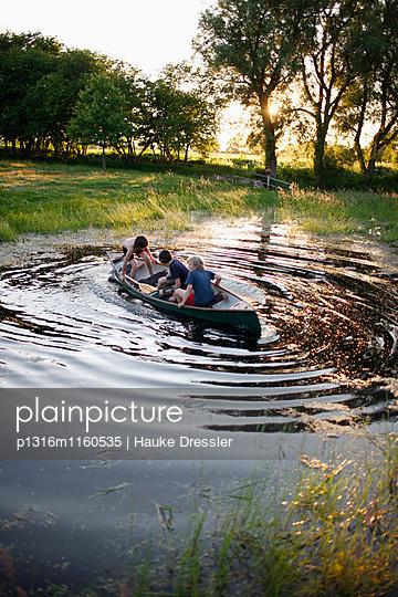 Drei Jungen in einem Kanu auf einem Teich, Haus Strauss, Bauernkate in Klein Thurow, Roggendorf, Mecklenburg-Vorpommern, Deutschland - p1316m1160535 von Hauke Dressler