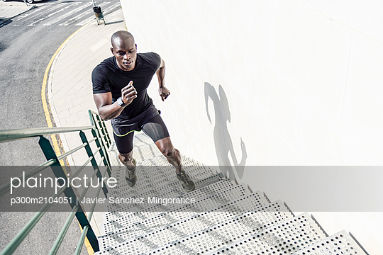 Man in black sportswear running up staircase - p300m2104051 by Javier Sánchez Mingorance