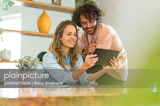 Happy couple looking at tablet together at home - p300m2276538 by Steve Brookland