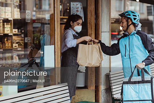 Young delivery man collecting order from female owner at delicatessen shop during COVID-19 - p426m2270647 by Maskot