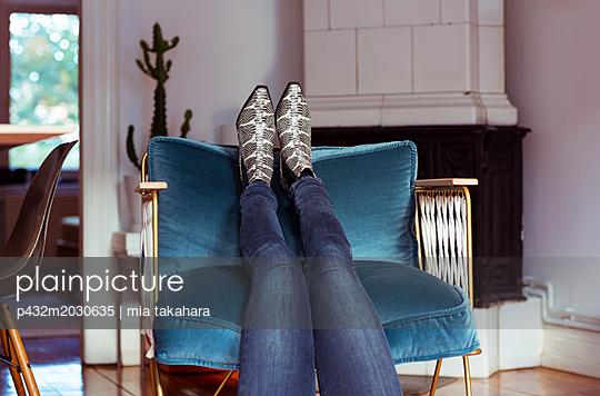 Junge Frau legt Füße hoch - p432m2030635 von mia takahara
