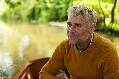 Happy man in boat on river - p1023m2262077 by Martin Barraud