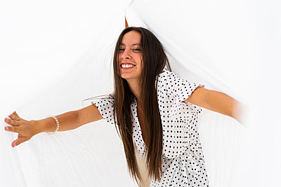 Portrait of young woman having fun with drying bed sheets on roof terrace - p300m2023966 von VITTA GALLERY
