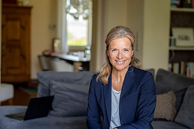 Portrait of smiling mature businesswoman at home - p300m2119659 by Jo Kirchherr
