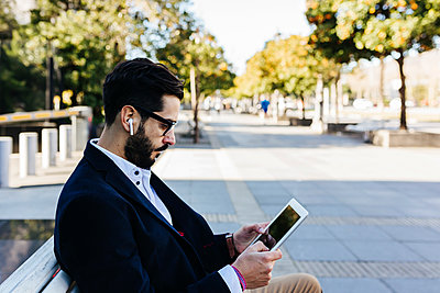 Businessman wearing in-ear headphones using digital tablet while sitting on bench - p300m2257508 by Xavier Lorenzo