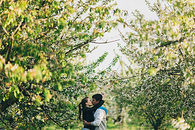 Caucasian couple kissing near trees - p555m1301818 by Kateryna Soroka