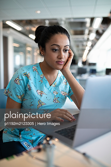 Nurse using laptop in hospital - p1192m2123305 by Hero Images