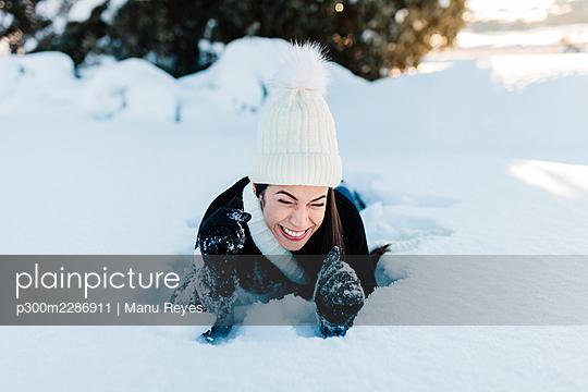 Cheerful woman lying on deep snow - p300m2286911 by Manu Reyes