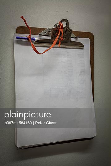 Klemmbrett mit Kugelschreiber an der Wand - p397m1584160 von Peter Glass