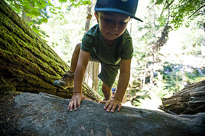 Young boy hiking, scrambling over large rock. - p1166m2212437 by Cavan Images