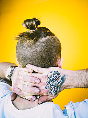 Man with pigtail and tattoo on his hand - p1267m2263412 by Jörg Meier