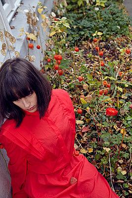 Frau sitzt in Blumenbeet - p1491m2163750 von Jessica Prautzsch