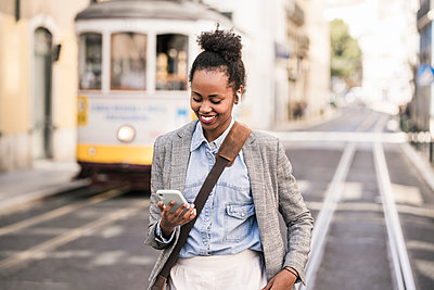 Smiling young woman with earphones and mobile phone in the city on the go, Lissabon, Portugal - p300m2144878 von Uwe Umstätter