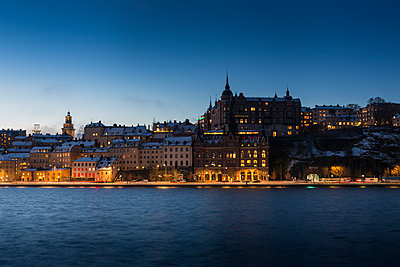 Buildings across water at night in Stockholm, Sweden - p352m1536575 by Calle Artmark